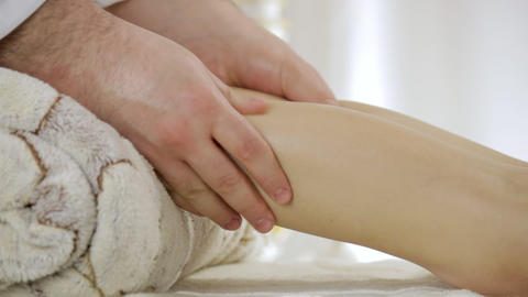 Doctor massage therapist relieves tension from gastrocnemius muscle of a young Footage