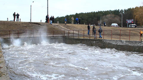 Water raging on dam during spring flood. Flooding of river in spring in town Live Action