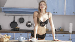 Young beautiful sexy Caucasian girl in black lingerie walking around the kitchen Footage