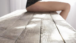 Sexy female buttocks sit on a wooden table, temptation, sunlight in the Footage