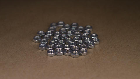 Metal nuts on craft paper rotating table Live Action
