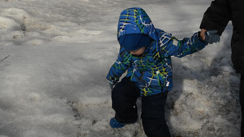 A small child walks on such loose snow in the Park in the spring, holds the hand Footage