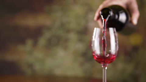 Close up male hand pouring red wine in glass from bottle slow motion Footage