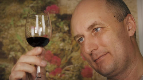 Face man looking on red wine in glass before tasting. Man drinking red wine Footage