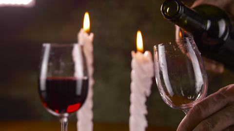 Male hand pouring red wine in glass from bottle on candle background Footage