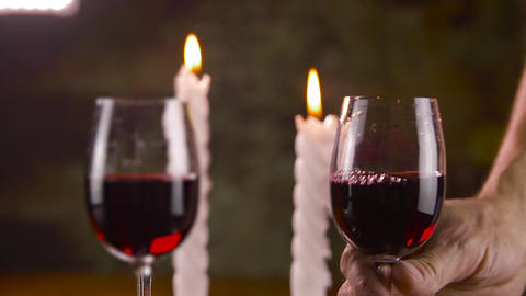 Man putting on table glass with red wine with candle light for romantic dinner Image