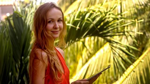 Girl Surfs Internet Using Tablet against Palms Footage