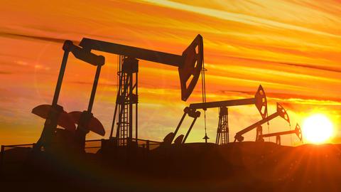 Looped working oil pump jacks against dusk Animation