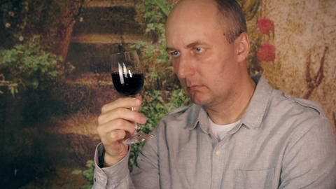 Adult man drinking red wine from glass and enjoy good taste close up Live Action