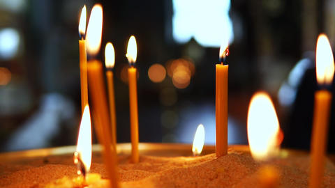 A lot of lighted candles standing in sand in the Christian Orthodox Church Footage