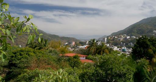 Establishing shot pan of houses and apartments built on a lush mountain forest Footage