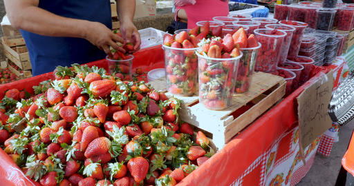 Man packing strawberries into plastic containers at a busy farmers' market while Footage