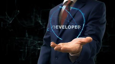 Businessman shows concept hologram Developer on his hand Live Action