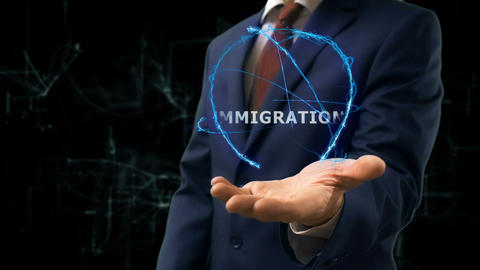 Businessman shows concept hologram Immigration on his hand Footage