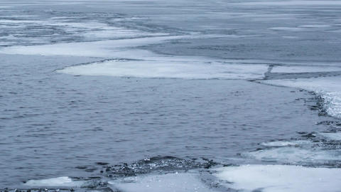 Timelapse of water waves on partly frozen lake with blocks of ice Footage
