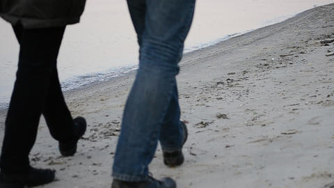 Legs of man and woman walking on the beach step for step Live Action