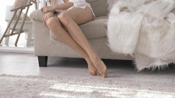 Sexy female Caucasian feet, legs, girl sitting on the couch, home comfort Footage