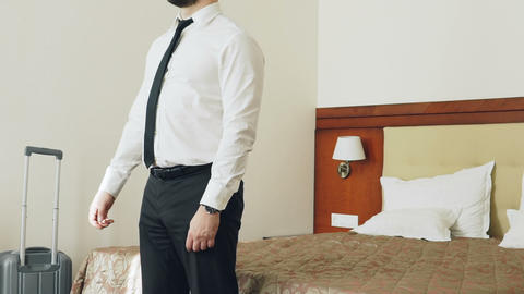 Slow motion of Happy businessman jumping on bed at hotel room and lying relaxed Footage