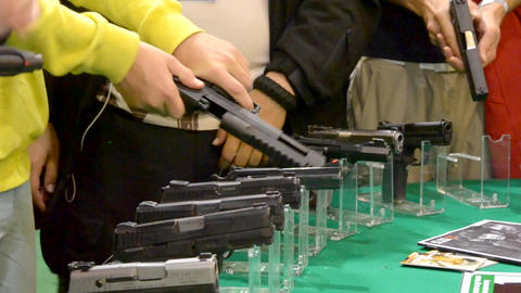 Many pistols on the table and hands Archivo