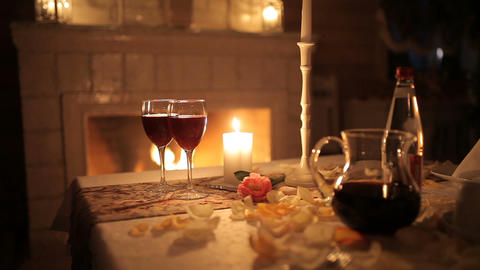 A loving couple dines by candlelight near the fireplace Live Action