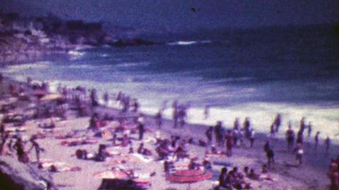 1964: Crowded tourist sunny ocean beach big waves crash on shore Footage
