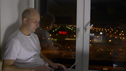 Confident man remote working with laptop on windowsill at night Footage