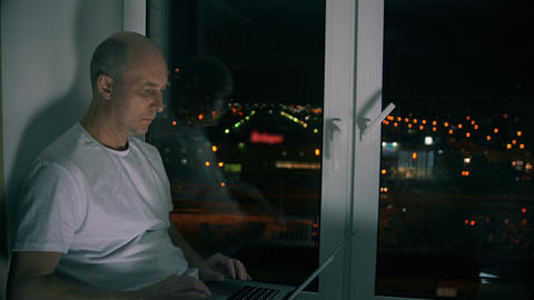 Serious mature man networking with laptop and sitting on windowsill at night Footage