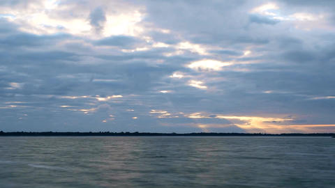 Time lapse of gorgeous clouds at dawn over water Live Action