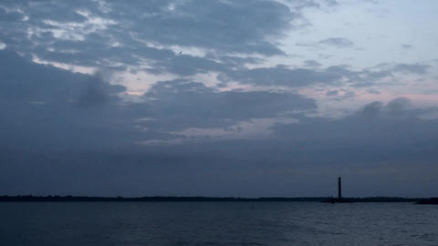 Time lapse of daybreak over water with lighthouse and clouds Footage