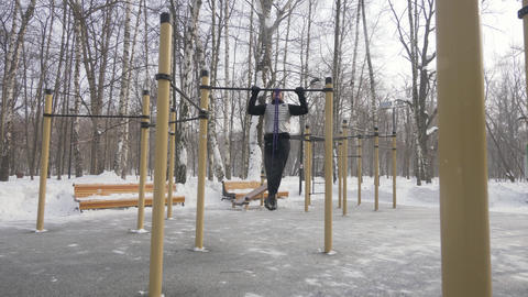 Fitness man training pull up exercise on sport ground. Outdoor winter training Live Action