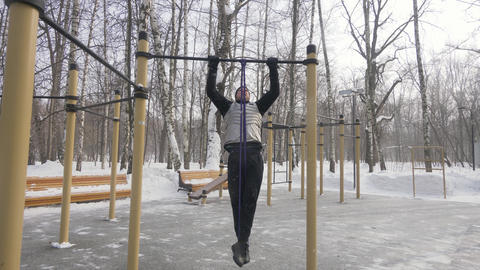 Man training pull up exercise with fitness expander on outdoor sport ground Footage