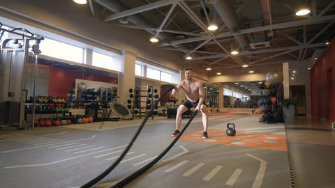 Athlete man training workout exercise with ropes in fitness club Footage