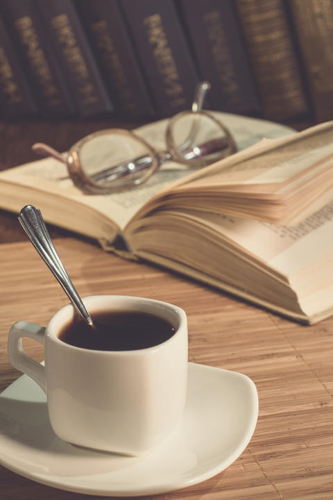 A cup of coffee and an open book on the table Fotografía