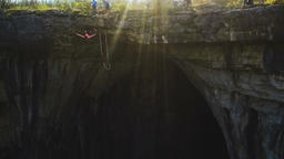 Girl in pink t-shirt bungee jumps from a cliff in Prohodna Cave Slow Motion Footage