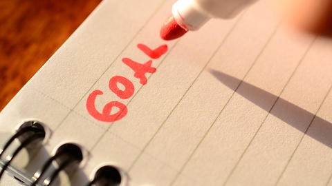 Hand writing the word GOALS with red marker in notepad Footage