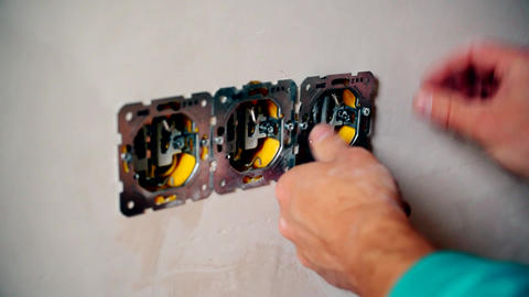 Electrician hands install electrical wall sockets Live Action