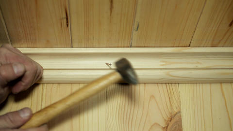 Male hands nailing a wooden skirting board Footage