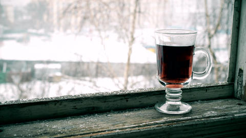 Snow falls with glass cup of tea on window sill Footage