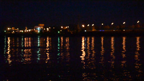 Urban landscape with city lights reflected in water in the evening at night Footage