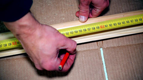 Hands measuring and marking a skirting board Footage