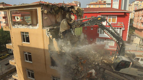 Bulldozer crushing the building at construction site. Demolition of a building Live Action