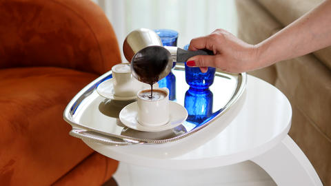 Woman hand serving Turkish Coffee with froth looks creamy in a silver tray. Live Action