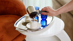 Woman hand serving Turkish Coffee with froth looks creamy in a silver tray. Archivo