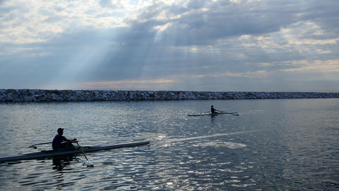 Single scull rowing competitors paddle on the tranquil lake with the ripples on Footage