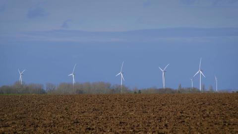 Rotating turbine towers on windmill field on blue sky background Footage