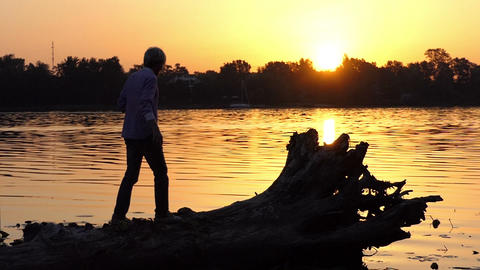 Blond man climbs the tree roots on a lake bank in slo-mo Footage