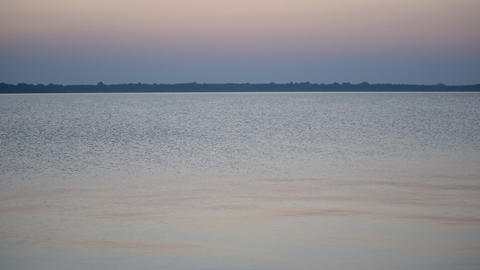 Calm water surface of a lake or river at dusk with colorful sky Footage