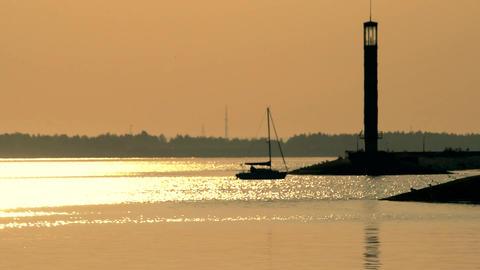 Sail boat enters a harbor at dusk near lighthouse Footage