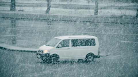 Slanting snow falling on background of blurred road Footage