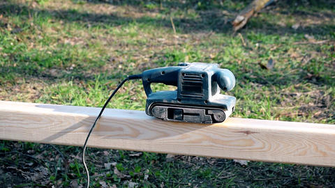 Polishing wooden beam with belt sander outdoors Archivo